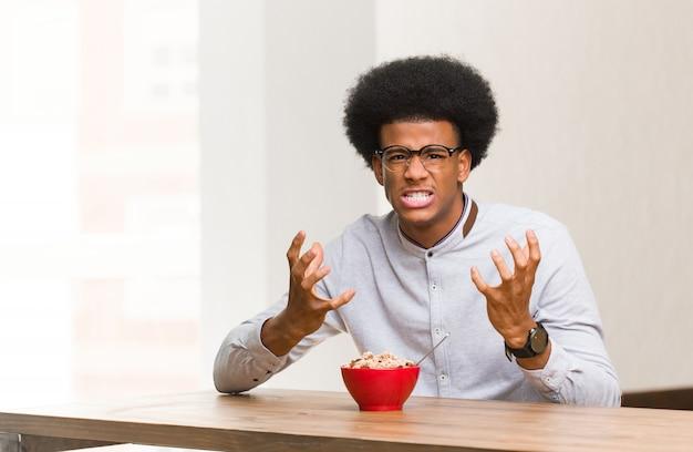 Jovem negro tomando um café da manhã com raiva e chateado