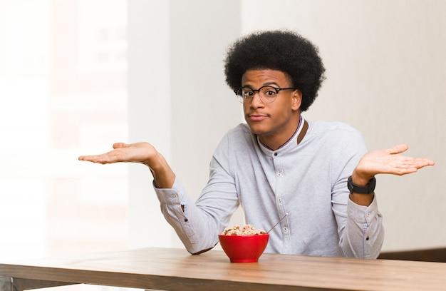 Jovem negro tomando um café da manhã duvidando e encolhendo os ombros