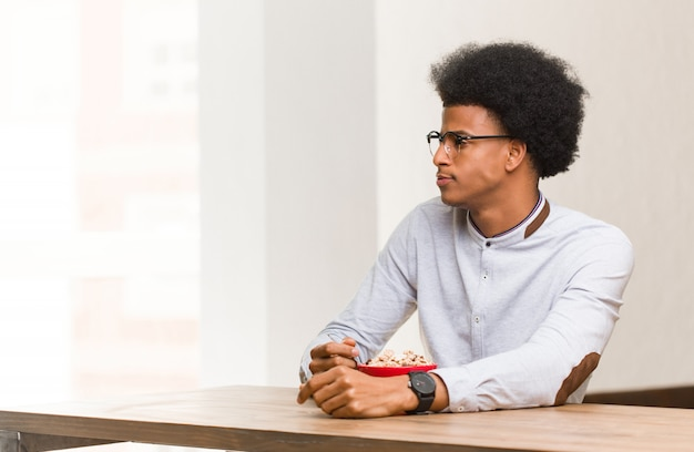 Jovem negro tomando um café da manhã no lado olhando para frente