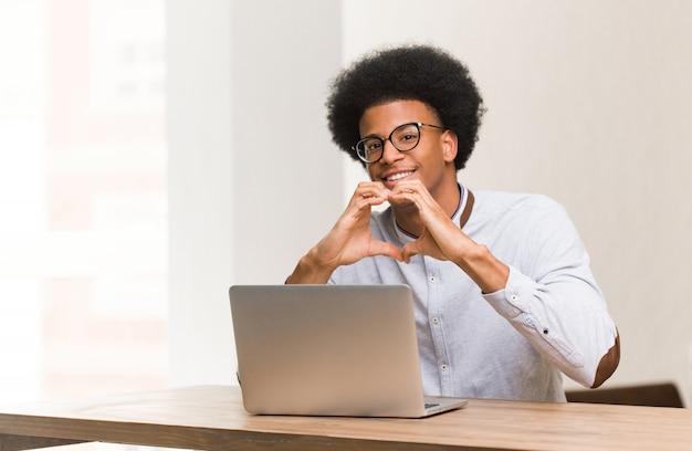 Jovem negro usando seu laptop, fazendo uma forma de coração com as mãos