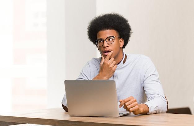 Jovem negro usando seu laptop relaxado pensando em algo olhando para um espaço de cópia