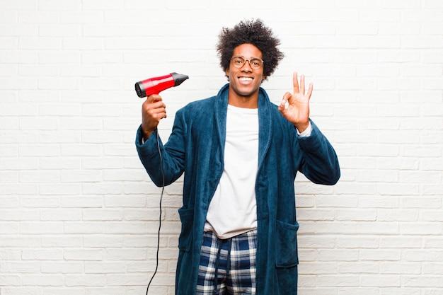 Jovem negro vestindo pijama com um secador de cabelo contra tijolo
