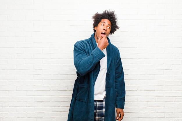 Jovem negro vestindo pijama com vestido com olhar surpreso, nervoso, preocupado ou assustado, olhando para o lado em direção ao espaço da cópia contra a parede de tijolos