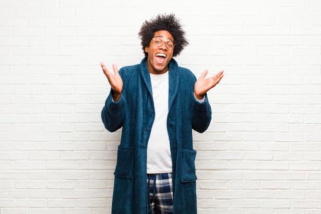 Jovem negro vestindo pijama com vestido olhando feliz e animado, chocado com uma surpresa inesperada com as duas mãos abertas ao lado do rosto contra o tijolo