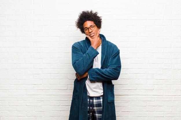 Jovem negro vestindo pijama com vestido olhando sério, pensativo e desconfiado, com um braço cruzado e mão no queixo, opções de ponderação contra a parede de tijolos