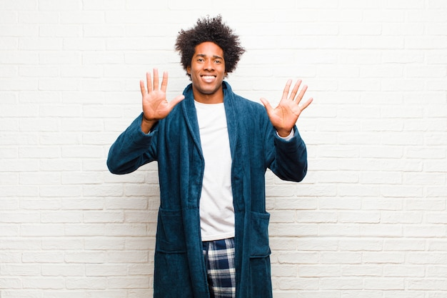 Jovem negro vestindo pijama com vestido sorrindo e olhando amigável, mostrando o número décimo com a mão para a frente, contando a parede de tijolos