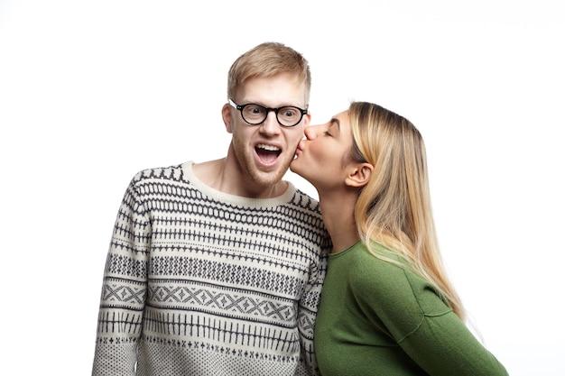 Jovem nerd barbudo e emocionado usando óculos, exclamando de entusiasmo, ficando chocado enquanto a bela mulher o beija na bochecha