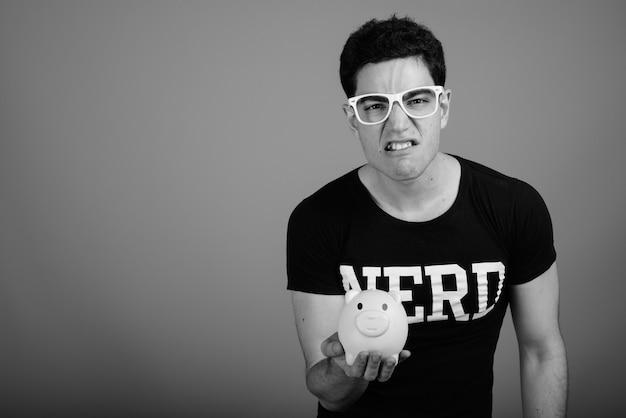 Jovem nerd bonito com óculos contra uma parede cinza