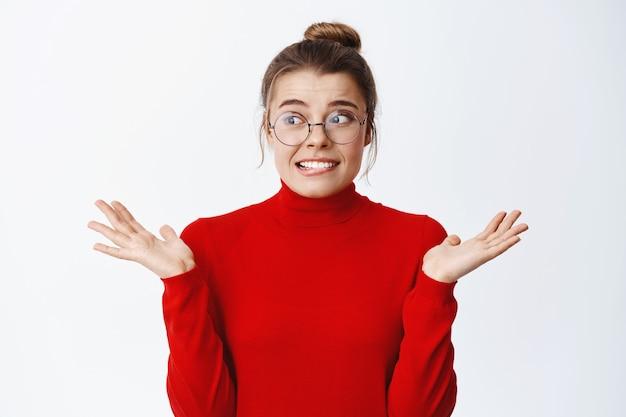 Jovem nervosa de óculos preocupada em cometer um erro, encolhendo os ombros e olhando de lado indecisa, não sabe de nada, não consigo entender, parede branca