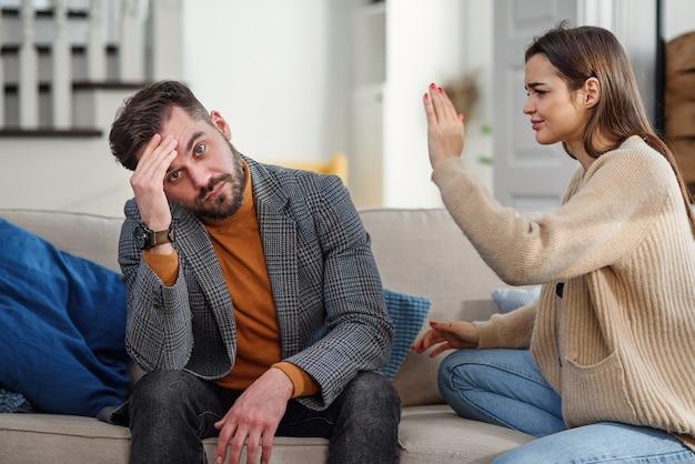 Jovem nervoso tentando não escuta sua namorada no quarto.