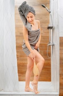 Jovem no banho faz uma massagem anticelulite com uma escova de drenagem de madeira. conceito de cuidados com a pele.