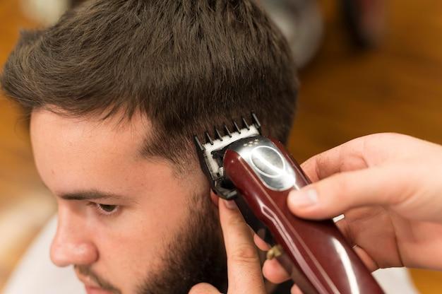 Jovem no barbeiro cortando o cabelo