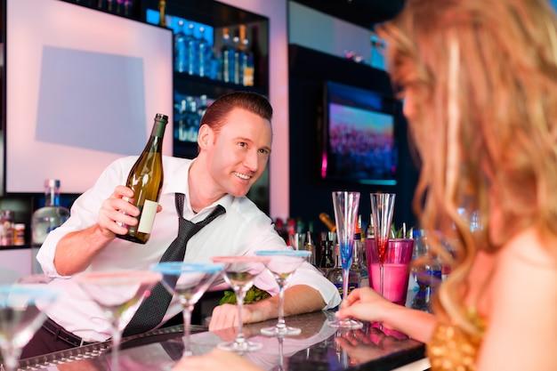 Jovem no clube ou bar bebendo champanhe