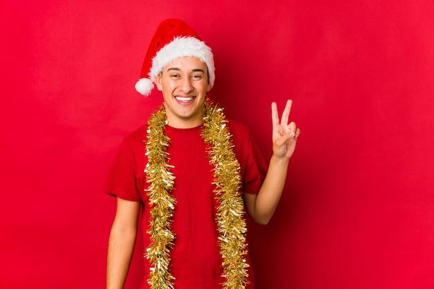 Jovem no dia de natal alegre e despreocupado, mostrando um símbolo de paz com os dedos.