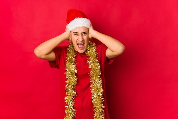 Jovem no dia de natal, cobrindo os ouvidos com as mãos, tentando não ouvir som muito alto.