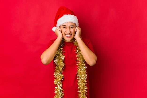 Jovem no dia de natal, cobrindo os ouvidos com as mãos.