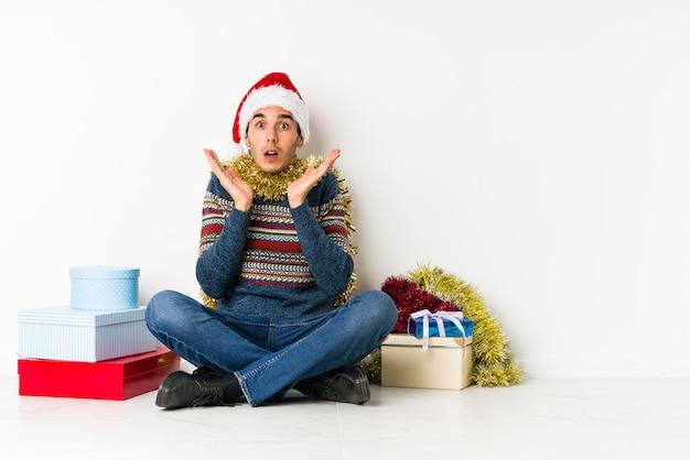 Jovem no dia de natal, duvidando e encolher os ombros os ombros em questionar o gesto.