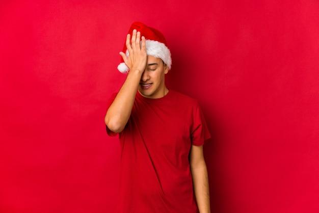 Jovem no dia de natal esquecendo algo, batendo na testa com a palma da mão e fechando os olhos.