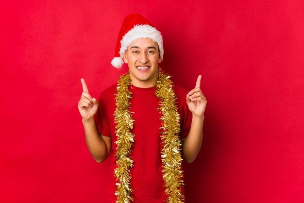 Jovem no dia de natal indica com os dois dedos dianteiros, mostrando um espaço em branco.