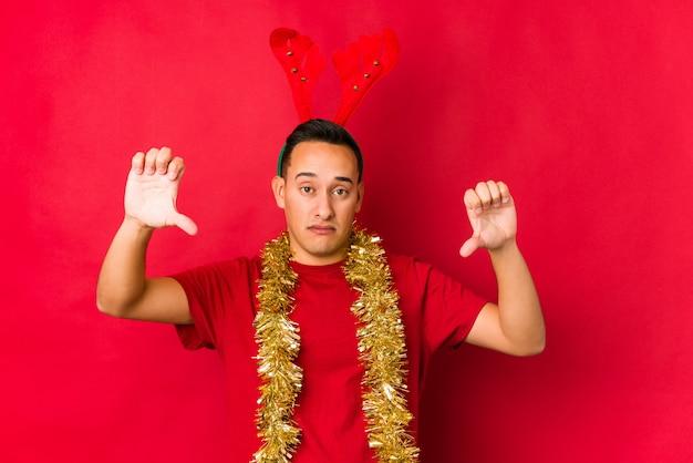 Jovem no dia de natal, mostrando o polegar para baixo e expressando antipatia.