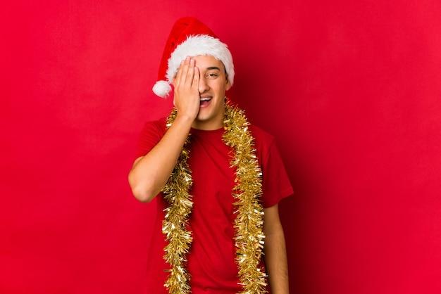 Jovem no dia de natal se divertindo cobrindo metade do rosto com palm.
