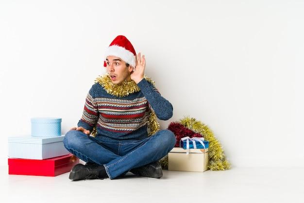 Jovem no dia de natal, tocando a nuca, pensando e fazendo uma escolha.
