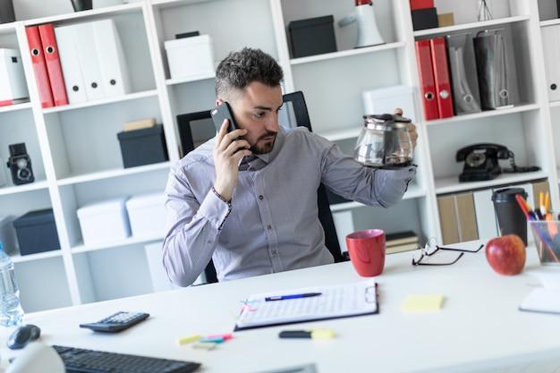 Jovem no escritório está sentado à mesa, falando ao telefone e olhando para a cafeteira.