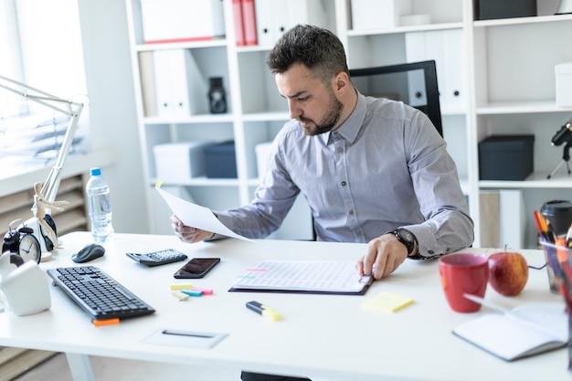 Jovem no escritório se senta à mesa e trabalha com documentos.