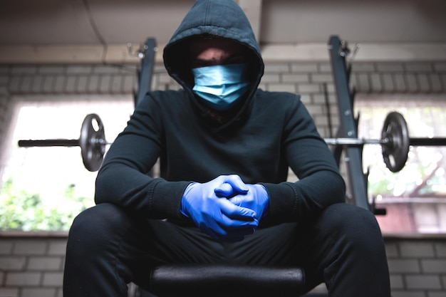 Jovem no ginásio com pesos e máscara protetora e luvas para coronavirus, covid-19, fitness e conceito de corona