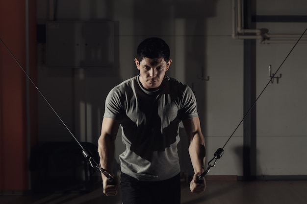Jovem no ginásio de exercícios sobre os músculos peitorais, a redução nas mãos de crossover. luz forte e tonificante.