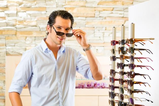 Jovem no oculista comprar óculos de sol