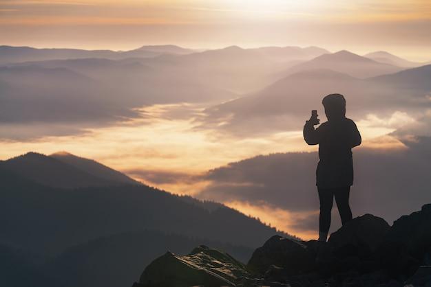 Jovem no pico da montanha fotografa ao telefone uma bela paisagem montanhosa ao nascer do sol.