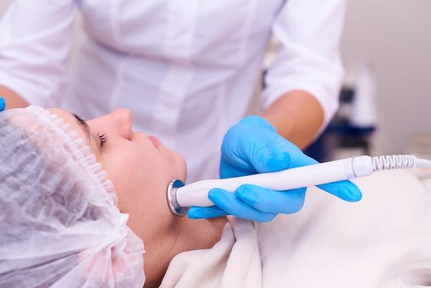 Jovem no procedimento de lifting facial em uma clínica de cosmetologia