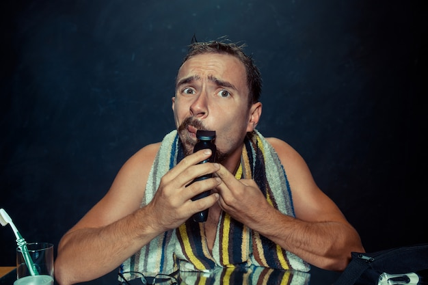 Jovem no quarto, sentado na frente do espelho, coçando a barba