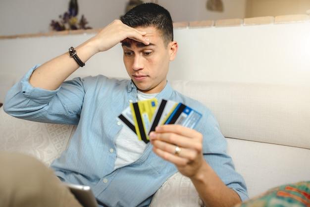 Jovem no sofá em casa com um tablet, fazendo compras online. segurando muitos cartões de crédito.