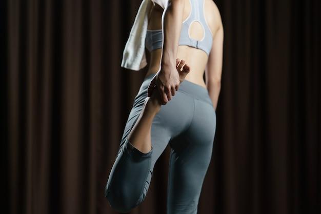 Jovem no sportswear cinza exercer em casa, fazendo alongamentos antes de executar