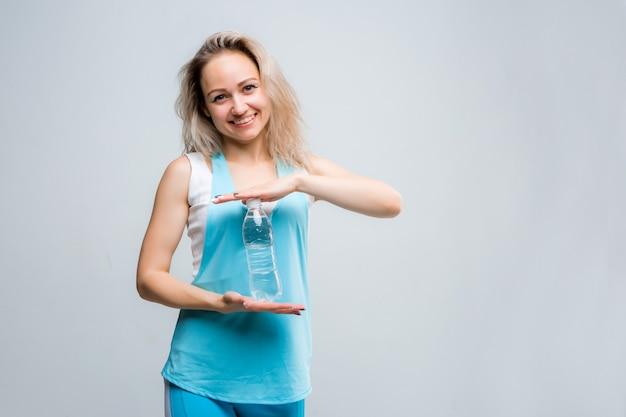 Jovem no sportswear com uma garrafa de água limpa em uma parede branca