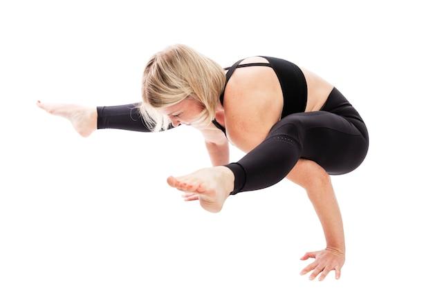 Jovem no sportswear preto em pose de ioga. estilo de vida saudável. isolado sobre o fundo branco