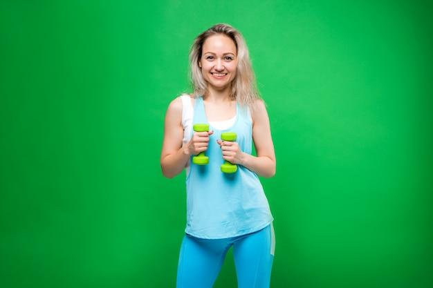 Jovem no sportswear segurando halteres em uma parede verde, espaço para texto