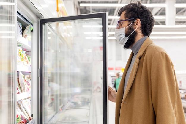 Jovem no supermercado no departamento com alimentos congelados. uma morena com uma máscara médica durante a pandemia de coronavírus.