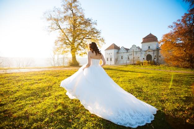 Jovem noiva andando no prado flor