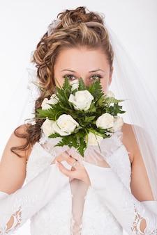 Jovem noiva atraente com o buquê de rosas brancas