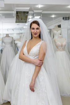Jovem noiva atraente com vestido de noiva em salão moderno