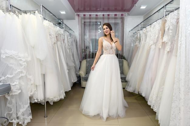 Jovem noiva atraente escolhendo vestido de noiva em salão de casamento