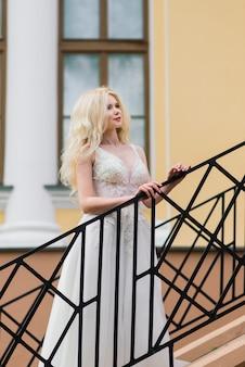 Jovem noiva atraente loira com cabelo encaracolado caminhando no parque e sorrindo, casamento conceito