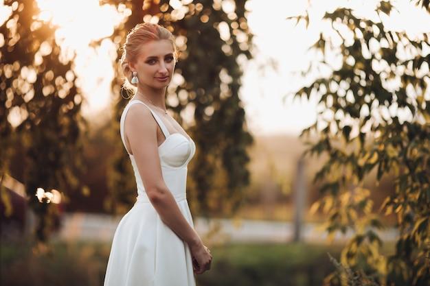 Jovem noiva caucasiana em um vestido branco com um lindo corte de cabelo caminhando sozinha para o jardim de verão