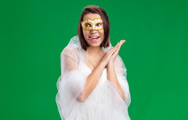Jovem noiva com lindo vestido de noiva usando máscara de baile de máscaras, olhando de lado feliz e alegre, mostrando a língua em pé no verde