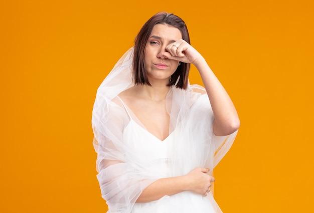 Jovem noiva com um lindo vestido de noiva e uma expressão triste esfregando os olhos em pé na parede laranja