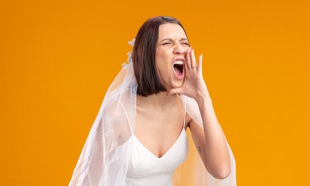Jovem noiva com um lindo vestido de noiva gritando bem alto ou chamando alguém de mão dada perto da boca, em pé sobre a parede laranja
