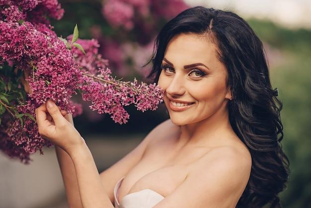 Jovem noiva com um vestido luxuoso de flores em um jardim lilás florido, close-up